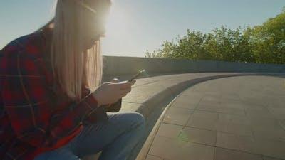 Cute Skateboarder Sitting on Skateboard Using Mobile Phone at Daybreak
