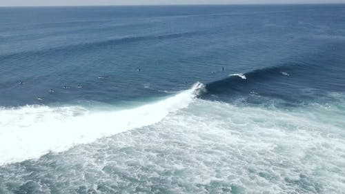 Aerial Shot Barreling Waves with Surfers Doing Surf Stunts and Paddling in Sea