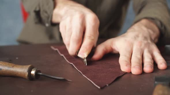 Guy Working with Leather Using Crafting Tool at Workshop