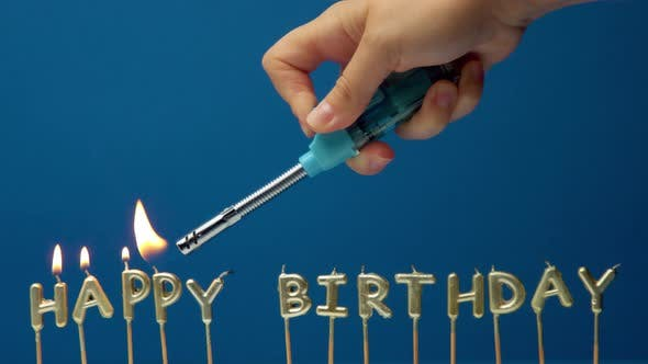 The Hand Makes Lights Candles Happy Birthday with a Lighter