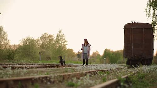 Young Woman Walks at Camera with Her Dog at Old Abandoned Railway
