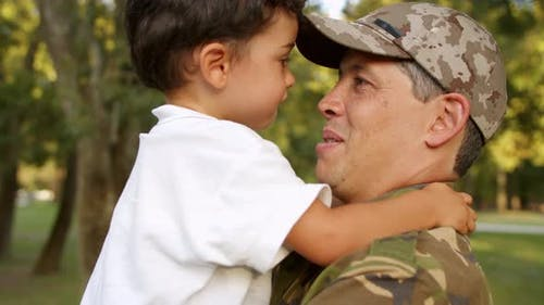 Happy Military Daddy Holding Little Son in Arms