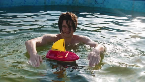 Cover Image for Young Man Playing with a Toy Boat in the Swimming Pool