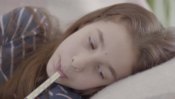 Thumbnail for Close Up Sad Sick Girl Lying in Bed with a Thermometer in Mouth. Concept of a Sick Child. Medicine