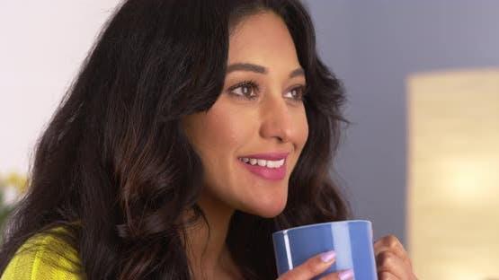 Hispanic woman enjoying her cup of coffee