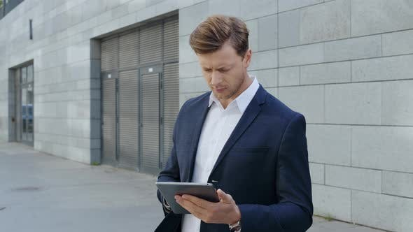 Businessman Working on Digital Tablet in City. Manager Browsing Internet on Pad