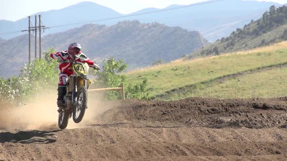 Thumbnail for A young man riding a motocross dirt motorcycle.
