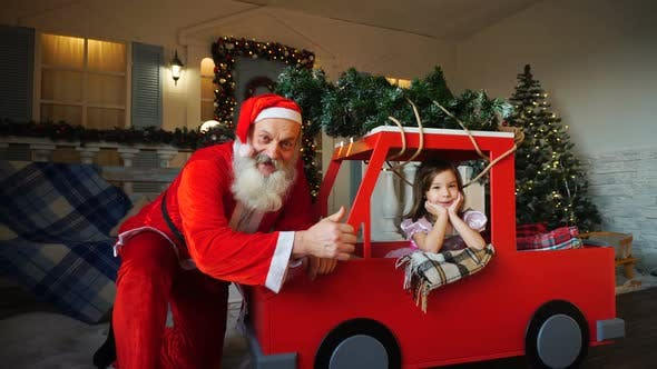 Cover Image for Funny Father Christmas Doing Thumbs Up Near Gladden Little Princess with Waving Hand.