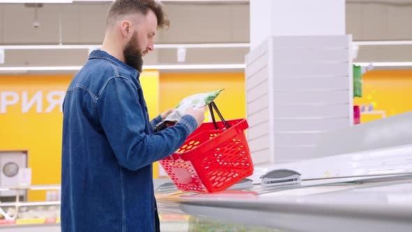 Man is Shopping in Supermarket Choosing Frozen Vegetables