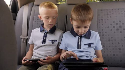 Two Little Boys are Sitting in the Backseat of a Car with a Phone and Tablet