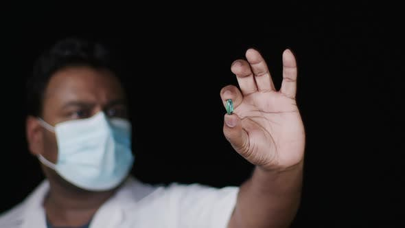 Cover Image for Lab Technician Holds Green Capsule