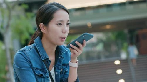 Woman hold with mobile phone in city