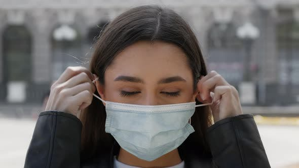 Happy Young Woman Taking Off Protective Face Mask Posing Outdoors