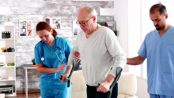 Thumbnail for Young Male Doctor and Woman Helping Old Man