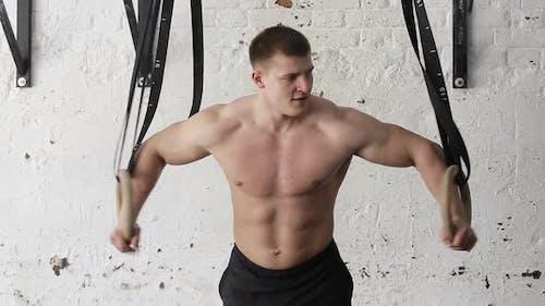 Mann macht Übungen an Turnringe. ein muskulöser Athlet für ein Crossfit-Workout.
