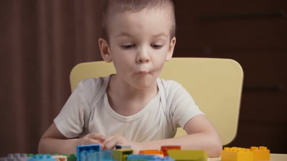 Thumbnail for Footage Little Happy Boy Playing with Colourful Blocks of a Constructor at Home