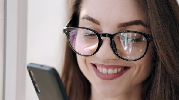 Thumbnail for Beautiful Woman in Glasses Is Near the Window Smiling