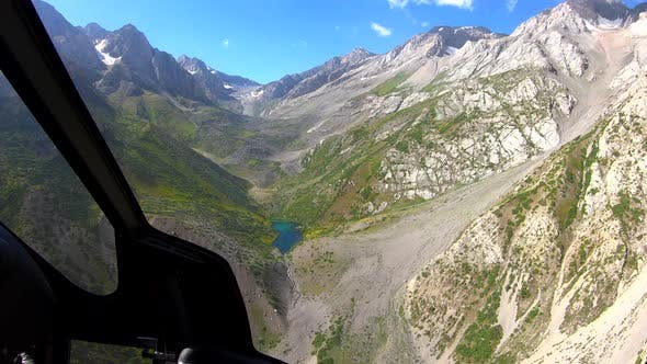 View From the Helicopter Cockpit Over Rocky Mountains and Lake