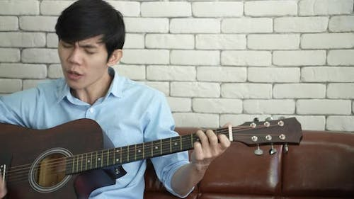 young Asian man playing guitar music and sing a song relax to record video live streaming