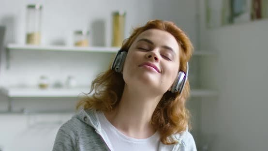 Thumbnail for Young Woman Is Listening Music in Wireless Headset at Home