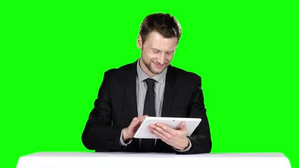 Cover Image for Businessman Sitting at the Table and Uses Laptop. Green Screen