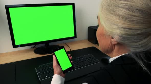 Thumbnail for Old Caucasian Woman Works on Computer and Smartphone in Home - Green Screen