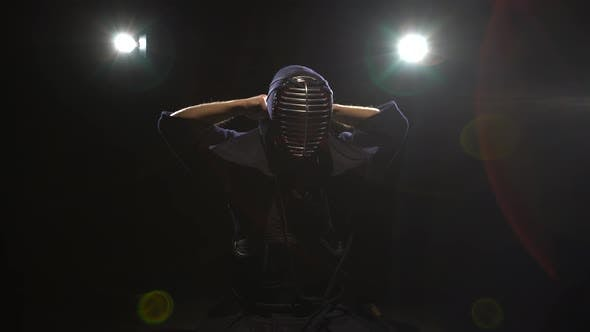 Thumbnail for Athletic Kendo Warrior Is Putting on Helmet and Lacing It at Background Spotlights