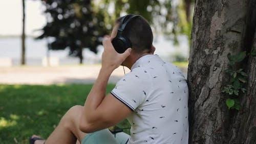 Man Puts on Big Headphones Leaning on Tree