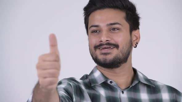 Thumbnail for Portrait of Young Happy Bearded Indian Man Giving Thumbs Up