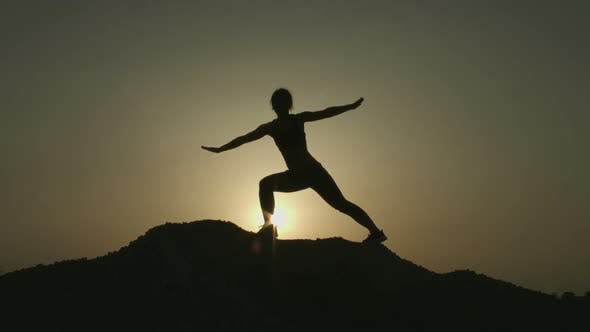 Thumbnail for Silhouette of Woman Practicing Yoga Alone on Top of Mountain in the Evening