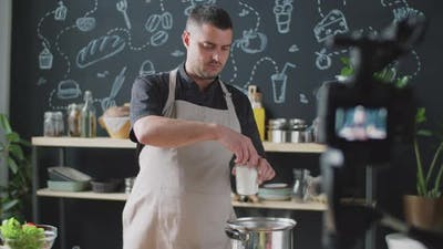 Male Vlogger Cooking and Speaking on Camera
