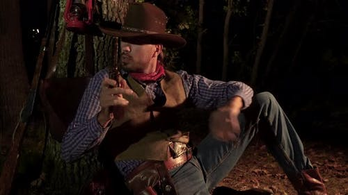 Cowboy with a Handgun in the Forest at Night