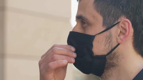 Coronavirus Is Defeated. Man Takes Off a Protective Mask.
