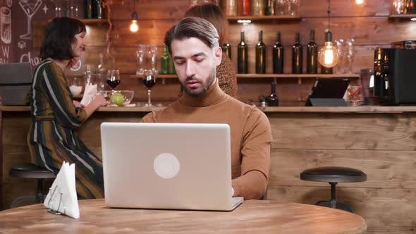 Hipster Freelancer Being Served Coffee While Working at His Laptop