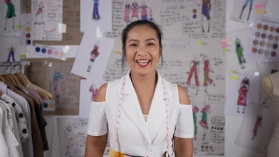 Asian attractive woman standing in office of online clothes shop