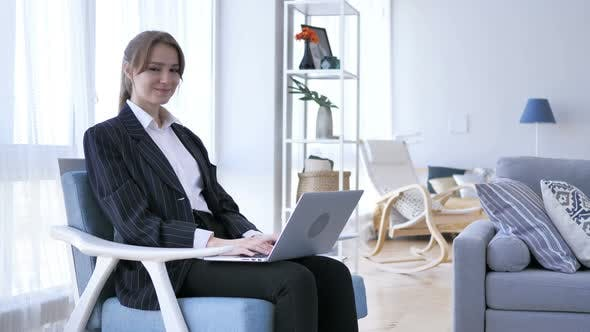 Thumbnail for Young Woman Working On Laptop and Looking at Camera