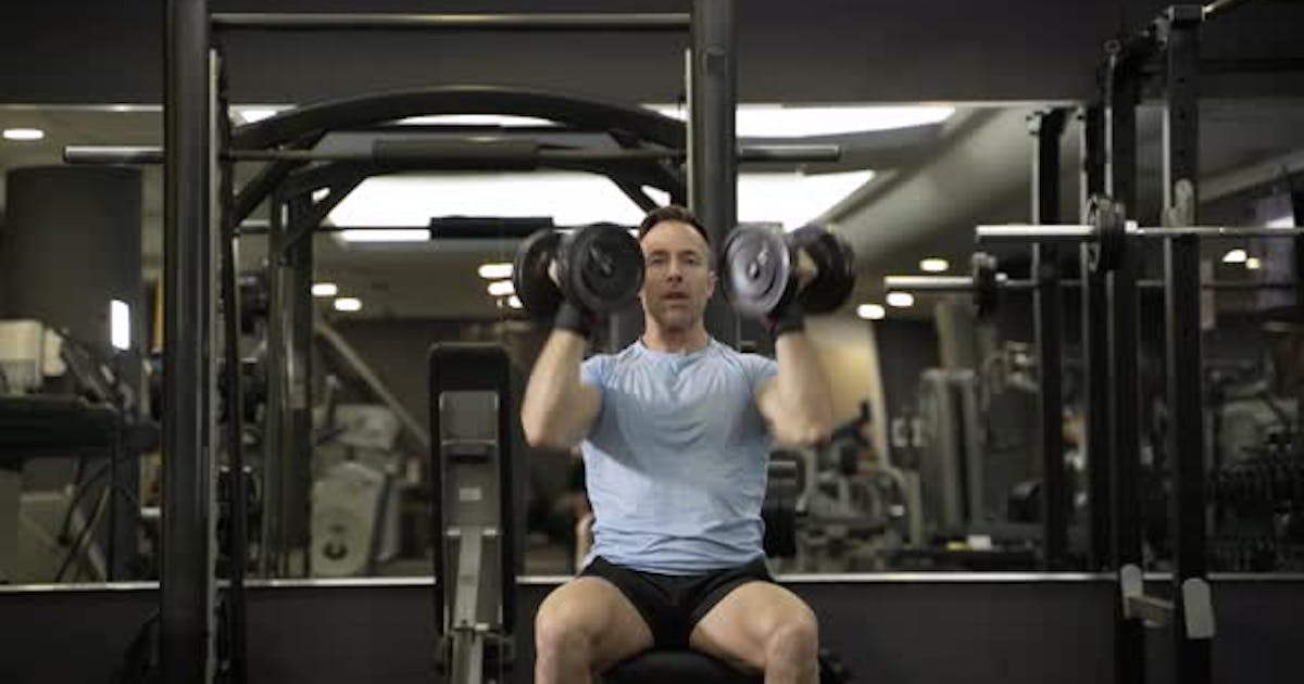 Muscular man holding dumbbell above the head at the gym.