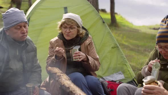 Thumbnail for Senior Woman Sitting with Friends by Campfire and Enjoying Canned Food
