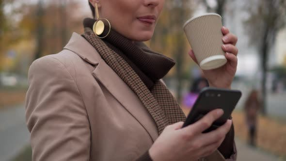 Thumbnail for Young Woman Drinks Coffee and Uses Smartphone on Street