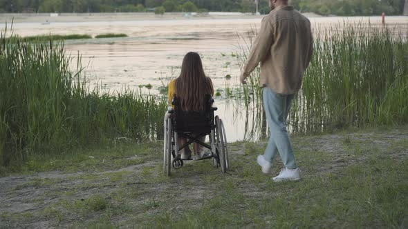 Thumbnail for Back View of Loving Man Coming To Disabled Woman on Wheelchair and Hugging Girlfriend. Happy