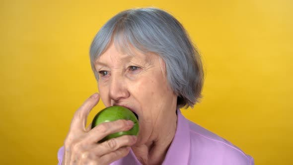 Thumbnail for Cheerful Elderly Woman Eating Apple