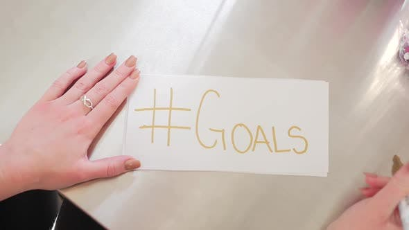 Thumbnail for Female Hands Writing Hashtag Goals On A White Piece Of Paper