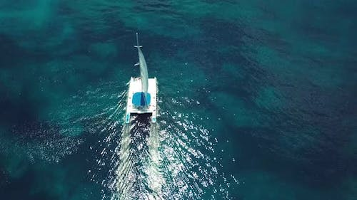drone shoot of the catamaran in the saona island in the caribbean sea with blue water in a sunny day