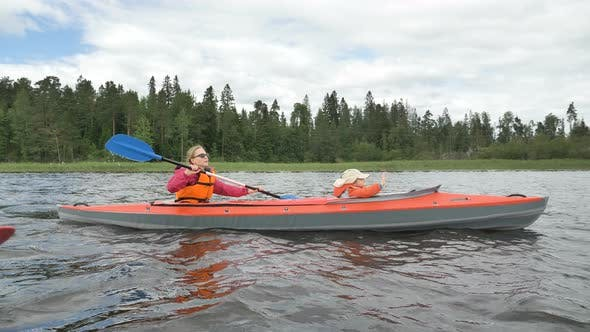 Thumbnail for Lady in Glasses Rows Kayak with Daughter Sailing Along Lake