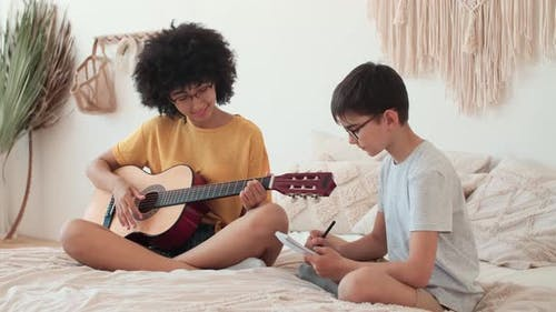 Afro American Girl Teaches Boy to Play Guitar While Sitting on Bed at Home