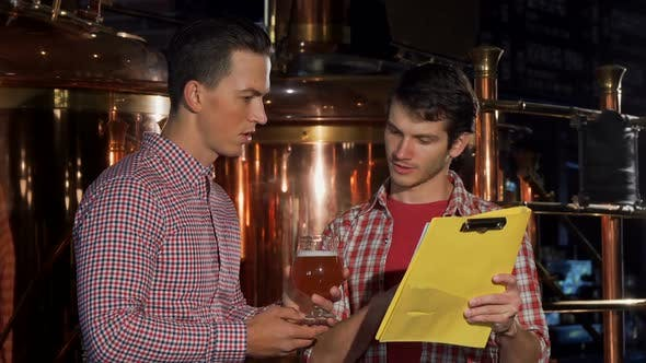 Two Brewers Examining Craft Beer, Working at the Brewery