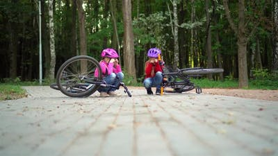 Two little girls in protective helmets collided on bicycles and cry.