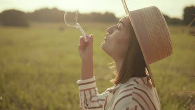 Young woman in hat blowing soap bubbles