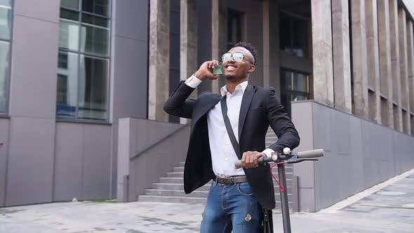 Thumbnail for Black-Skinned Office Worker which Walking with His Own Electric Scooter and Talking on Phone