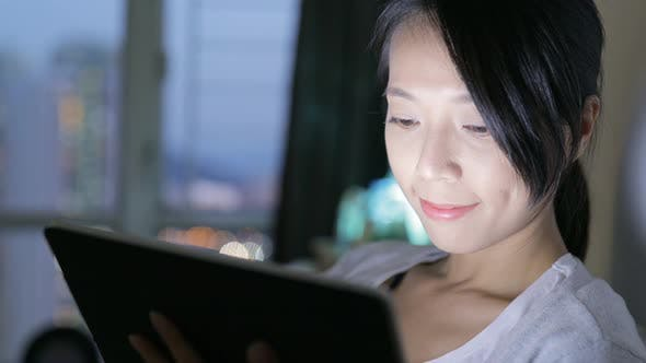 Thumbnail for Woman using tablet computer at home